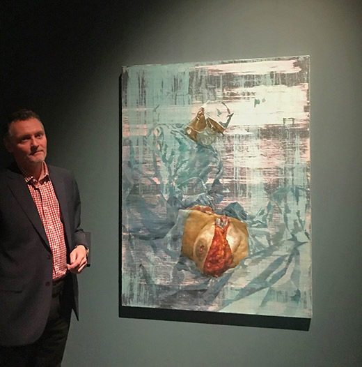 Cosmetic surgeon Miles Berry poses next to artwork by artist Jonathan Yeo
